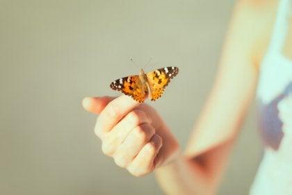 kadının parmağına konmuş bir kelebek