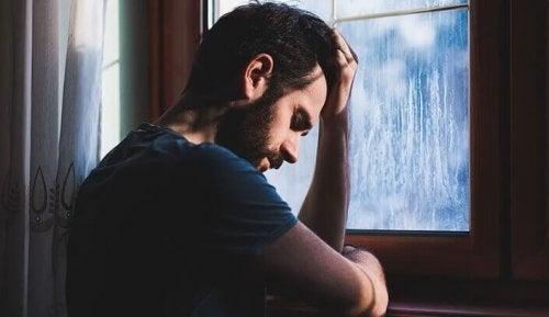 pencere önünde oturan üzgün adam