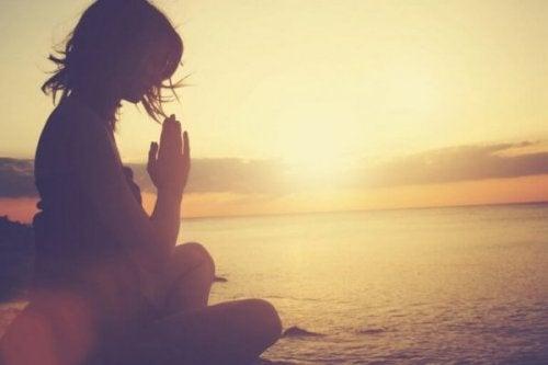 su kıyısında meditasyon yapan kadın