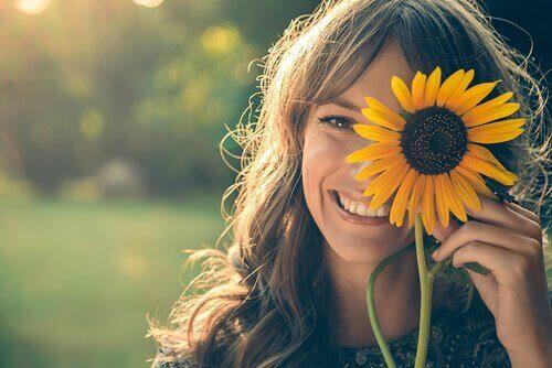 çiçek tutan ve gülümseyen kadın