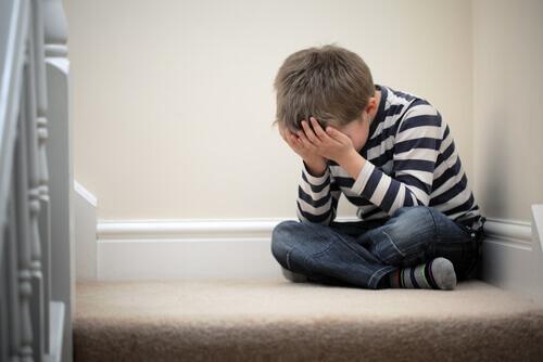 bir köşede çökmüş kalmış çocuk
