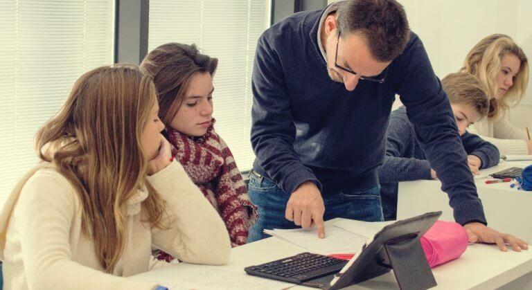 sınıfta öğretmen öğrencilerine yardımcı oluyor