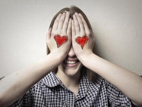 ellerine kalp çizen kadın gözlerini kapatıyor