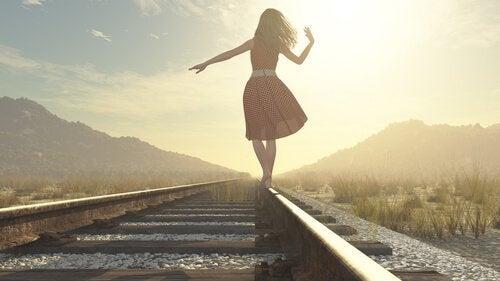 tren raylarının üzerinde yürüyen kadın