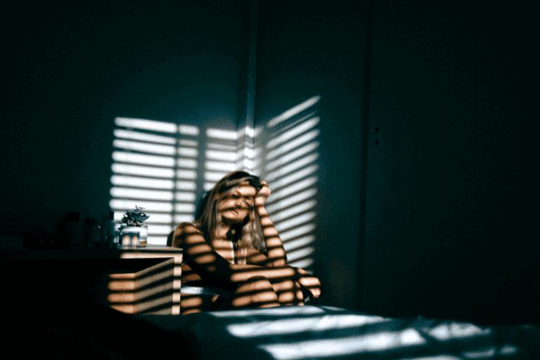 yatağında oturan mutsuz kadın