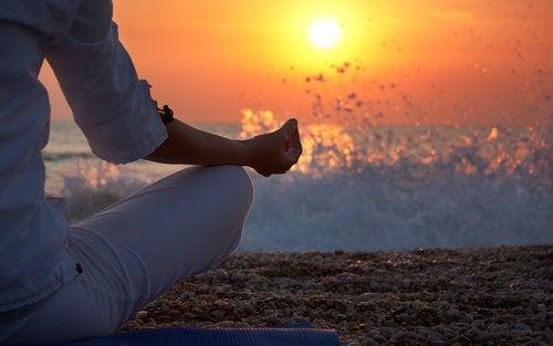 Deniz kenarında meditasyon yapan kadın