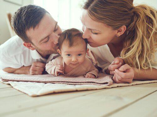 bebeklerini öpen ebeveynler