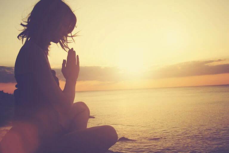 kadın sahilde meditasyon yapıyor