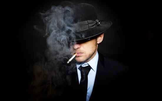 siyah takım elbiseli adam sigara içiyor
