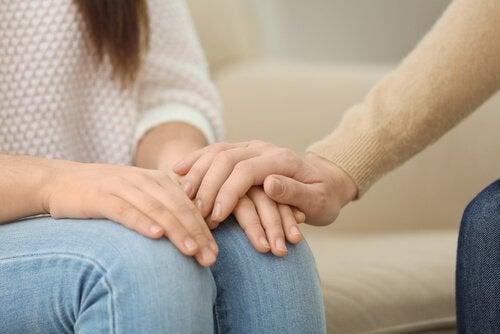 hastasının elini tutmuş psikolog