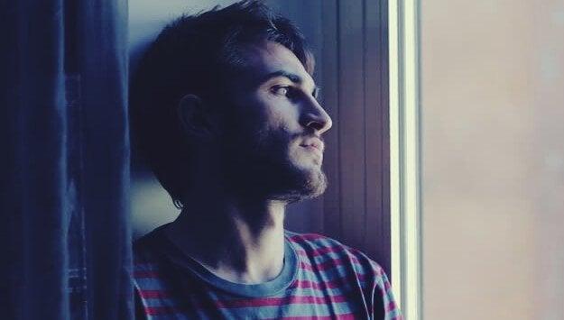 çizgili tişörtlü camdan bakan adam