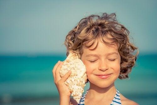 çocuk deniz kabuğu dinliyor
