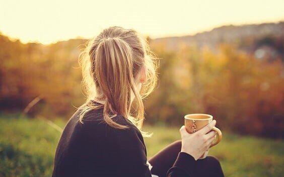 kahvesiyle bahçede oturan kadın