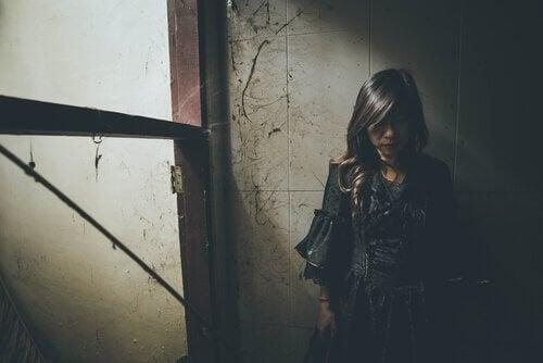 karanlıkta duvara yaslanmış duran kadın