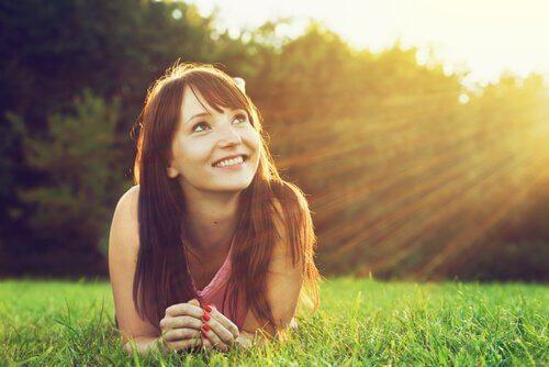 çimlerden uzanmış gülümseyen kadın