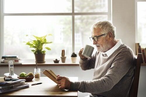 kahve içip kitap okuyan yaşlı adam