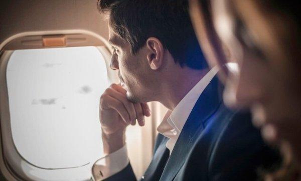 uçakta dışarı bakan adam