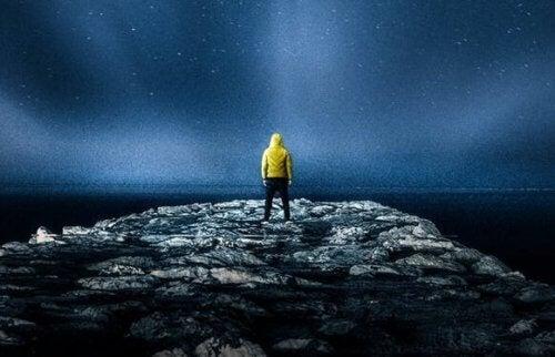 gece vakti kayalıkta duran bir adam