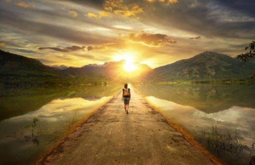 gün batımına doğru yürüyen insan