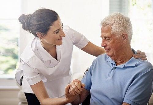 yaşlı adamla ilgilenen hasta bakıcı
