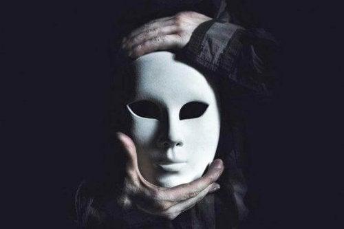 elinde maske tutan karanlık