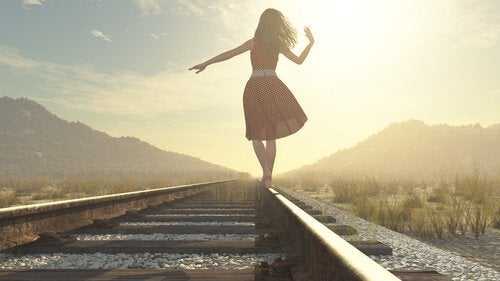 tren rayları üzerinde yürüyen kadın