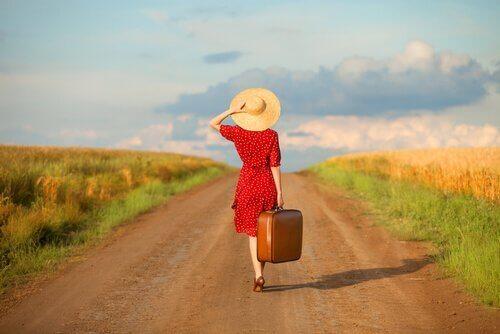 yolda elinde bavulla yürüyen kadın