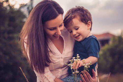 çiçeğe bakan anne çocuk