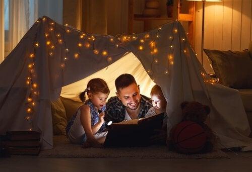 çadırda kitap okuyan baba ve çocukları