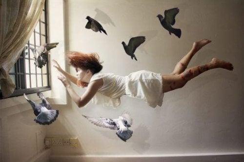 etrafında kuşlarla uçan kadın