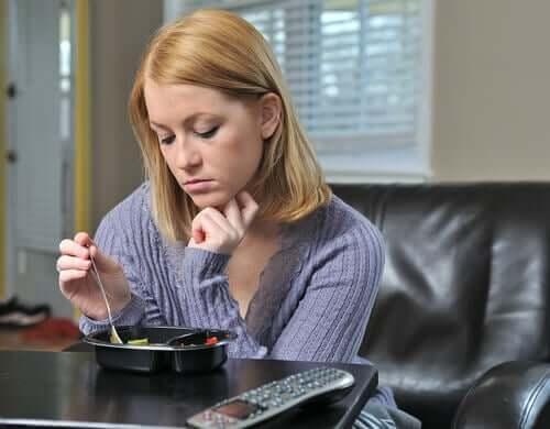 üzgün bir halde yemeğiyle oynayan kadın