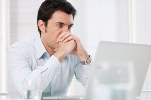 endişeli bir biçimde laptop önünde oturan adam
