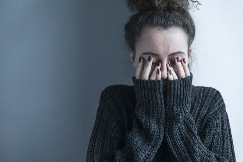 yüzünü elleriyle kapatan depresyondaki kadın
