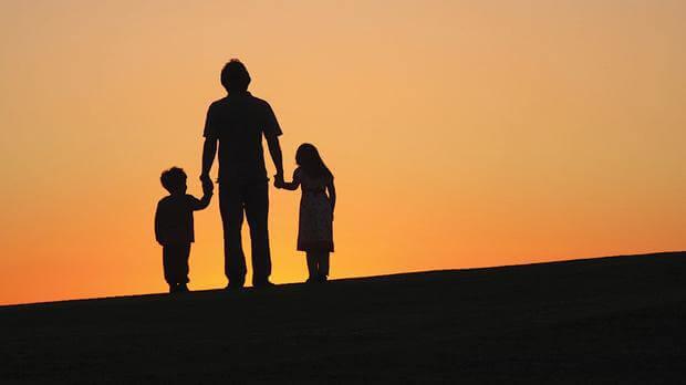 Çocuklarının ellerinden tutan baba