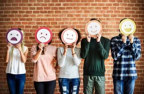 Yüzlerinin önünde üstünde duyguları simgeleyen yüzler olan kağıtlar tutan 5 kişi.