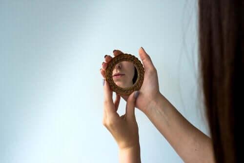 Bir kadın elinde tuttuğu bir el aynasına bakıyor.
