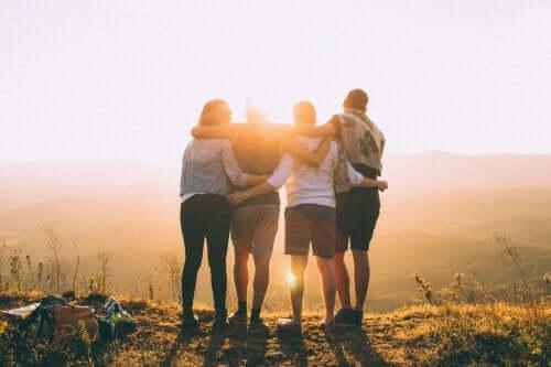 Sarılarak gün batımına bakan dört kişi.