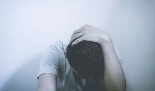 Bir adam, başını ellerinin arasına almış şekilde duruyor.