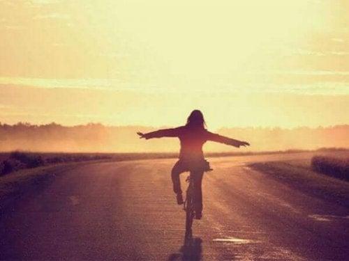 Gün batımına doğru bisiklet süren bir kadın.