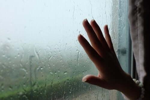 Dışarıda yağmur yağarken cama koyulmuş bir el fotoğrafı.