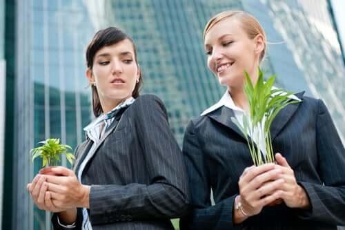 Çiçeği daha fazla büyümüş iş arkadaşına kıskançlıkla bakan kadın.
