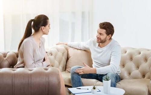 Kanepede oturmuş konuşan bir çift.