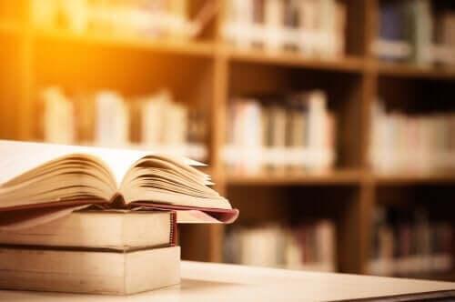 Biri açık olan üç kitap ve arka planda kitap rafları.