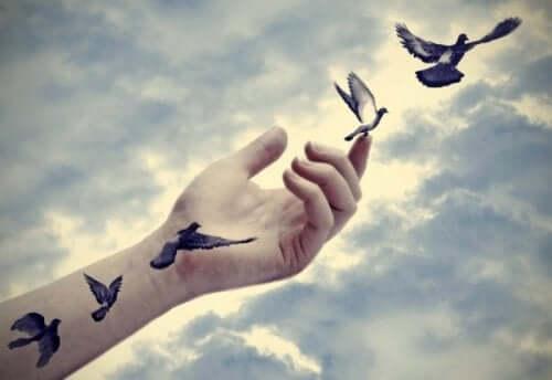 Gökyüzüne uzanmış bir koldaki kuş dövmeleri koldan çıkıp uçmaya başlıyor.