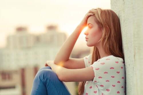 Duvara dayanmış oturan mutsuz bir kadın.