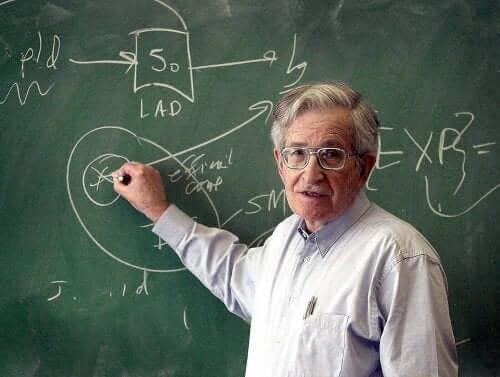 Noam Chomsky bir tahtaya bir şeyler yazarken poz veriyor.