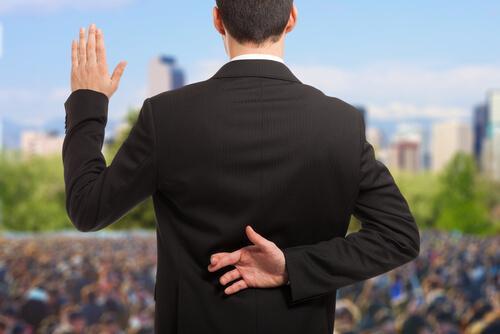 Arkasında parmaklarını yalan söylediğini belirtir şekilde çaprazlamış bir politikacı.