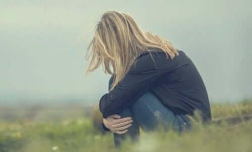 Kırsal bir bölgede diz çökmüş şekilde oturan kadın.