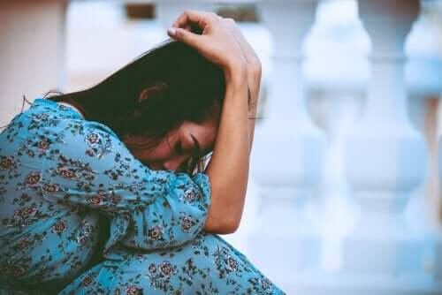 Mavi elbiseli bir kadın başını ellerinin arasına almış şekilde oturuyor.