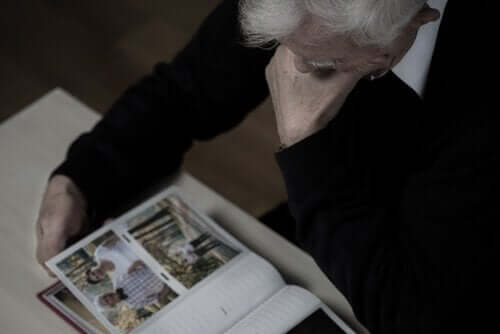 Yaşlı bir adam bir fotoğraf albümüne bakıyor.